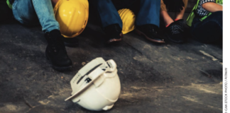 hard hat on ground with workers stock photo